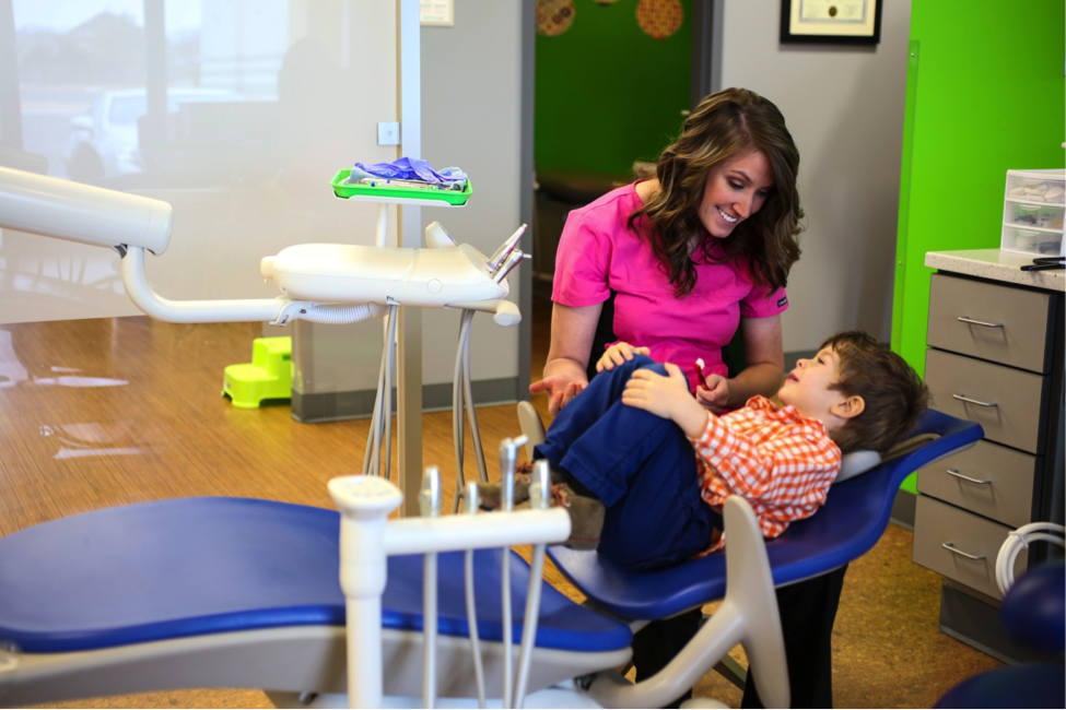 Child patient in chair with dental hygenist.