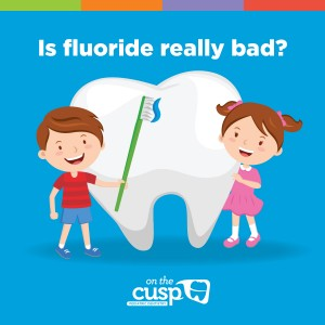 Two cartoon children one boy and one girl holding a toothbrush in front of a big tooth