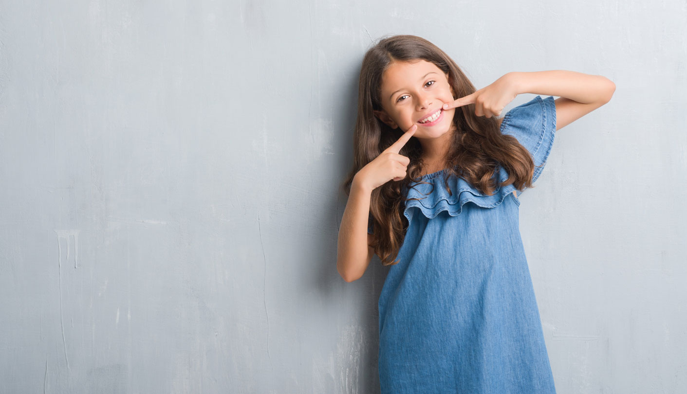 Young girl pointing to her smile with both hands