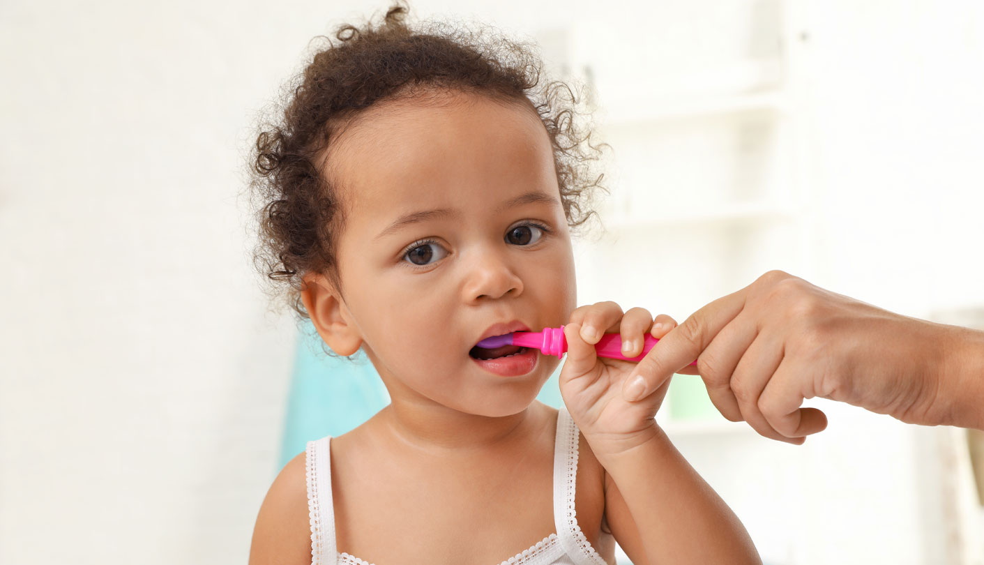 Female toddler brushing her teeth with a helping hand from mom