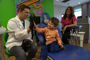 Young boy patient and Dentist high five after a dental exam