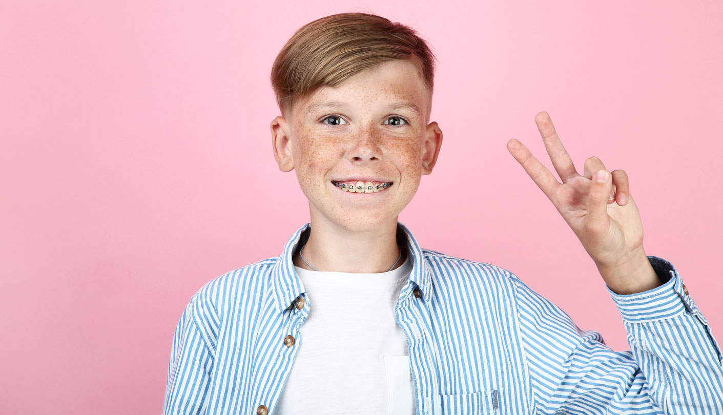 Young boy smiles wearing braces holding up two fingers