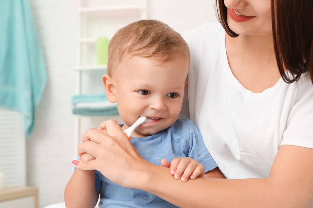 Baby boy brushing his teeth with a toothbrush while mom helps