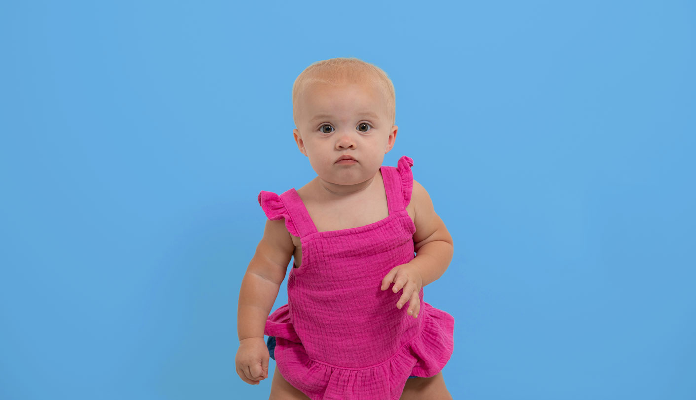 Female baby stands in front of blue background wearing a pink dress