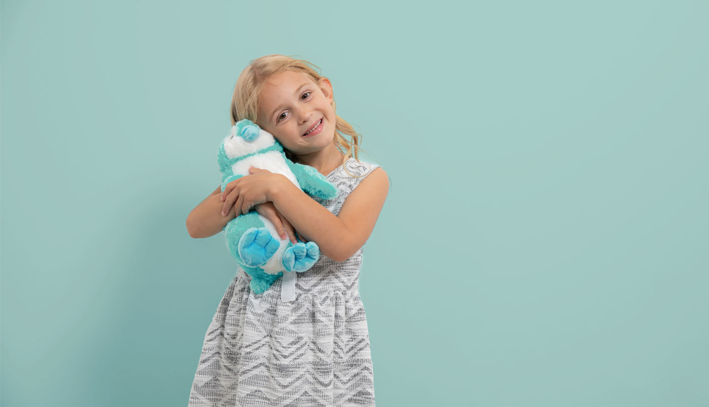 Female child holds a stuffed animal standing in front of a green background