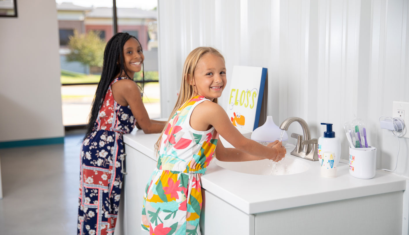 two girls smiling while washing hands