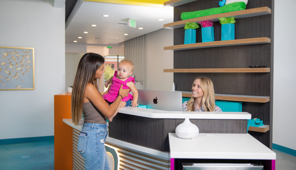 Mother sits female baby on the front desk counter at On the Cusp while the receptionist smiles at them both