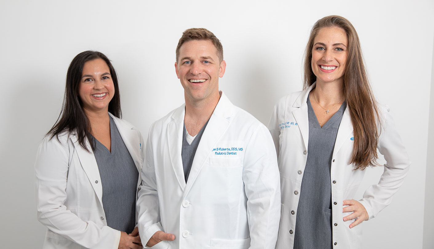 Three Pediatric dentists standing side by side smiling