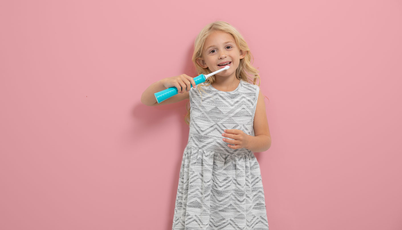 Female child stands in front of a pink background holding a toothbrush up to her teeth and smiling