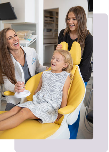 female child in a yellow dentist chair looking happy with female Dental Hygienist and Doctor smiling